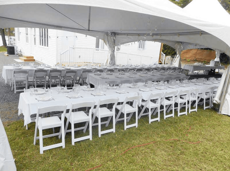 large white tent with tables aligned for wedding